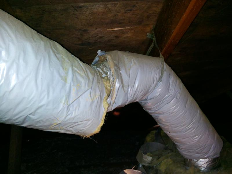 Photo shows damaged air duct in attic.